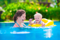 Mother and baby in a swimming pool. Mother and baby in swimming pool. Parent and child swim in a tropical resort. Summer outdoor activity for family with kids stock image