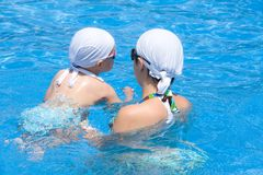 Mother and baby are swimming in swimming pool Stock Images