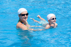 Mother and baby are swimming in swimming pool Royalty Free Stock Photos