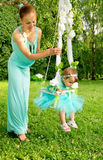 Mother and baby on a swing on nature Stock Photo