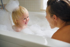 Mother and baby taking bath and playing with foam Stock Photography