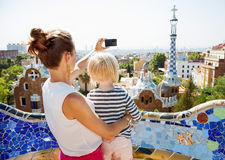 Mother and baby taking photos with digital camera at Park Guell Stock Photography