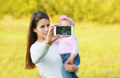 Mother and baby taking self-portrait on smartphone Stock Images