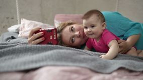 Mother and baby taking selfie with phone in bed stock footage