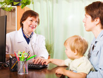 Mother with baby talking with friendly pediatrician doctor Royalty Free Stock Photos