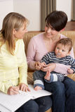 Mother With Baby Talking With Health Visitor. At Home royalty free stock images