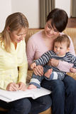 Mother With Baby Talking With Health Visitor At Ho. Me royalty free stock photography