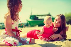 Woman spending time with kids on beach Stock Photos