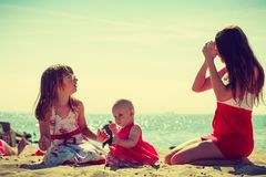 Woman spending time with kids on beach Royalty Free Stock Photo