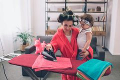 Mother and baby together engaged in housework Ironing clothes . Housewife and kid doing homework. Woman with little. Child in the living room. Homemaker doing stock photos