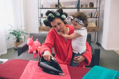 Mother and baby together engaged in housework Ironing clothes . Housewife and kid doing homework. Woman with little. Child in the living room. Homemaker doing Stock Photography