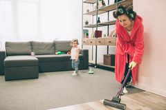 Mother and baby together engaged in housework. She is washing the floor of the mop. Housewife and kid doing homework. Woman with little child in the living Royalty Free Stock Photo