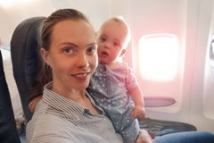 Mother and baby traveling on plane look at camera. Mother and baby traveling on plane and look at camera. Happy mom with a baby boy in her arms flying on a plane Royalty Free Stock Photography