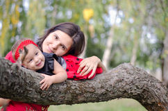 Mother and baby on the tree. Mother and her child cuddling on a branch of a tree royalty free stock photography