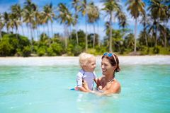 Mother and baby on tropical beach. Kids swim. Stock Image
