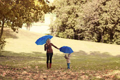 Mother and baby with umbrella walks in autumn park Royalty Free Stock Photo