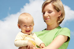 Mother with baby under blue sky Royalty Free Stock Photos