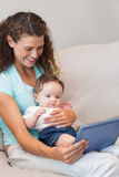 Mother and baby using digital tablet Stock Image