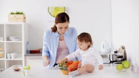 Mother and baby with vegetables at home kitchen stock footage
