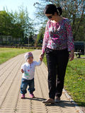 Mother and baby walk. Mother and toddler baby girl walk in a park stock images