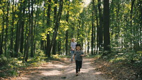 Mother and baby walk on country rural road in forest and then girl run toward the camera stock footage