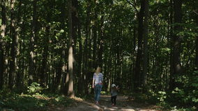 Mother and baby walk on country rural road in pine forest stock video
