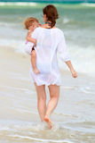 Mother and baby walking along beach Royalty Free Stock Photo