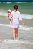 Mother and baby walking along beach Royalty Free Stock Photography