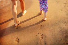Mother and baby walking along the beach. Stock Image