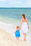 Mother and baby walking along tropical beach Royalty Free Stock Photos