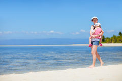 Mother with baby walking along tropical coast Stock Photography