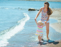 Mother and baby walking on beach Stock Photo