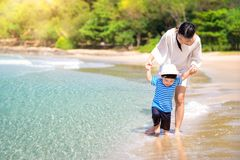 Mother and baby walking on the beach royalty free stock photos