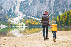 Mother and baby walking on lake braies in italy. Mother and baby walking on lake braies in south tyrol, italy. rear view royalty free stock photography
