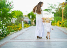 Mother and baby walking outdoors. Rear view Stock Photos