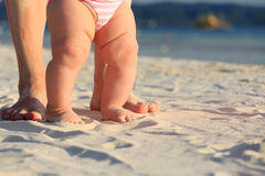 Mother and baby walking on sand beach Royalty Free Stock Photography