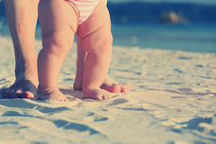Mother and baby walking on sand beach Stock Image