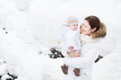 Mother and baby walking in a snowy park Royalty Free Stock Image