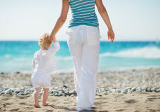 Mother and baby walking to sea. Rear view Royalty Free Stock Images