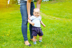 Mother and baby walking together on the grass in summer Stock Images