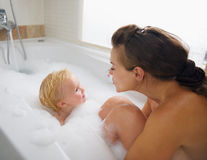 Mother and baby washing in foam filled bathtub Royalty Free Stock Image