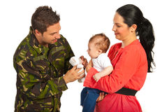 Mother and baby welcoming army dad. Mother and baby welcoming military father who gives to his child a fluffy bear toy isolated on white background stock images