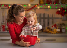 Mother and baby whisking dough in kitchen Stock Photography