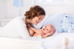 Mother and baby on a white bed Stock Images
