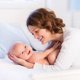 Mother and baby on a white bed Royalty Free Stock Photography