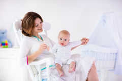 Mother and baby in white bedroom Royalty Free Stock Photo