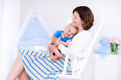 Mother and baby in white bedroom Stock Photography
