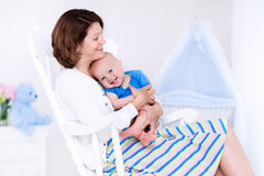 Mother and baby in white bedroom Stock Image