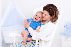 Mother and baby in white bedroom Stock Images