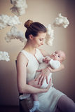 Mother with baby on white clouds Royalty Free Stock Image